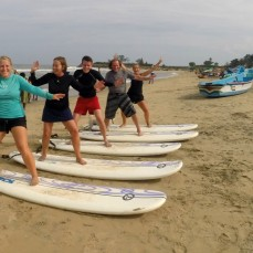 Happy international surf students practising on the beach