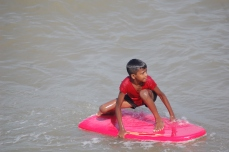 A young boy surfing a body board