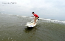 A surf student is taking one of her first green waves