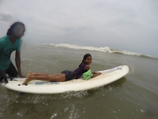 Mukesh helping a surf student to get her first waves
